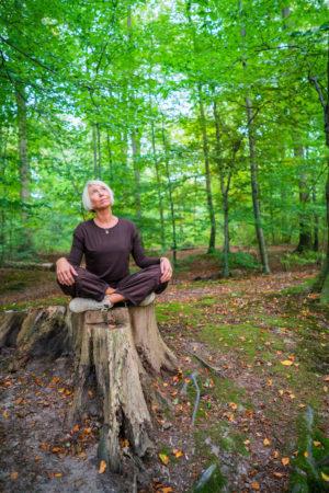 kvinde dyrker yoga midt i skoven