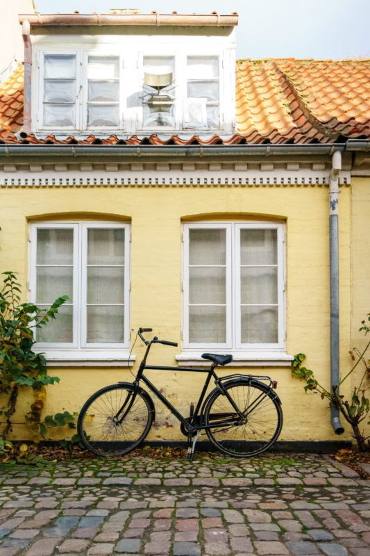 Cykel holder foran gult byhus i Odense